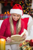 Pretty blonde in santa hat reading book at christmas time Royalty Free Stock Photography