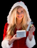 Pretty blonde in santa outfit opening gift Royalty Free Stock Photography