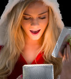 Pretty blonde in santa outfit opening gift Stock Photo