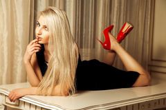 Pretty blonde with seduction look lying on table Stock Photography
