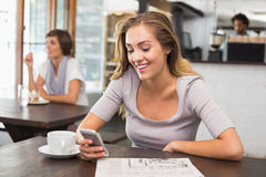 Pretty blonde sending text message Royalty Free Stock Image