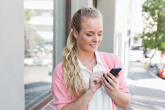 Pretty blonde sending a text message Royalty Free Stock Photos
