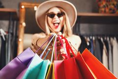 Pretty Blonde Shopaholic Holding Many Colorful Shopping Bags. Rich pretty blonde shopaholic woman wearing sunglasses and fashion hat holding many colorful royalty free stock images