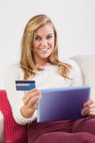 Pretty blonde shopping online with tablet pc Royalty Free Stock Photography