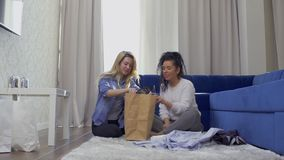 Pretty blonde shows a new stylish dress to her friend after shopping at home. Two young girls sits on floor at home after shopping among bags with purchases. The stock footage