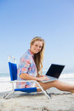 Pretty blonde sitting on beach using her laptop smiling at camera Royalty Free Stock Photos
