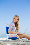 Pretty blonde sitting on beach using her laptop smiling at camera Stock Photography