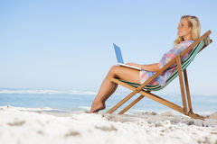 Pretty blonde sitting on beach using her laptop Royalty Free Stock Photo
