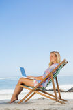 Pretty blonde sitting on beach using her laptop Stock Photography