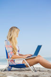 Pretty blonde sitting on beach using her laptop Stock Photo