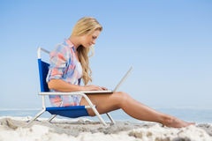 Pretty blonde sitting on beach using her laptop Stock Images