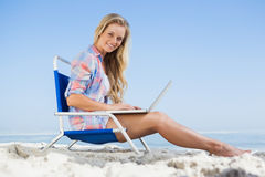Pretty blonde sitting on beach using her laptop Royalty Free Stock Images