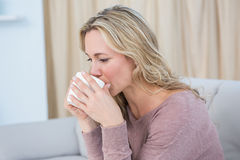 Pretty blonde sitting on couch drinking coffee Royalty Free Stock Images