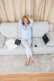 Pretty blonde sitting on couch near wirelesses technology Stock Photo