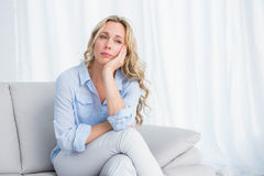Pretty blonde sitting on couch thinking Royalty Free Stock Photography