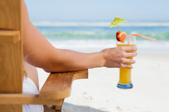 Pretty blonde sitting in deck chair with a cocktail Stock Photography