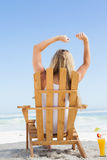 Pretty blonde sitting in deck chair with a cocktail Royalty Free Stock Image