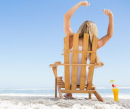 Pretty blonde sitting in deck chair with a cocktail Royalty Free Stock Images