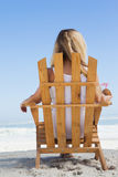Pretty blonde sitting in deck chair holding coconut drink Royalty Free Stock Photography