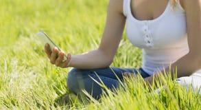 Pretty blonde sitting on grass sending a text Stock Photos