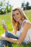 Pretty blonde sitting on grass sending a text Stock Images