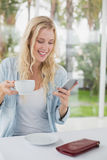 Pretty blonde sitting at table having coffee sending text Royalty Free Stock Image