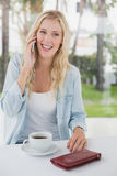 Pretty blonde sitting at table having coffee talking on phone Royalty Free Stock Images