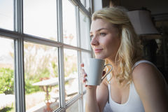 Pretty blonde sitting by the window having coffee Royalty Free Stock Image