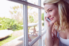 Pretty blonde sitting by the window on a phone call Stock Images