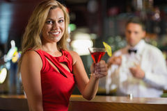 Pretty blonde smiling at camera with cocktail Royalty Free Stock Photo