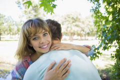Pretty blonde smiling at the camera in a park while hugging boyfriend Stock Images