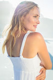 Pretty blonde standing at the beach in white sundress Stock Photos