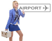 Pretty blonde stewardess in blue suit with a small suitcase Royalty Free Stock Photos