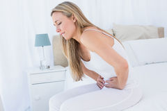 Pretty blonde suffering with stomach ache Stock Images