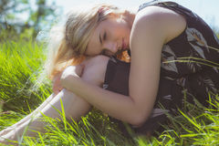 Pretty blonde in sundress sitting on grass Stock Photo
