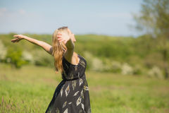 Pretty blonde in sundress standing with arms out Royalty Free Stock Photography