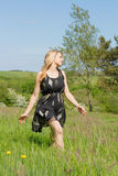 Pretty blonde in sundress walking through field Stock Images