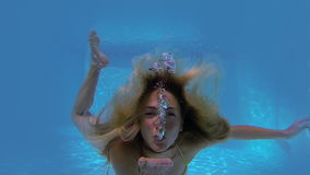 Pretty blonde swimming towards camera and blowing kiss stock video footage