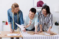 Pretty blonde tailor showing a sketch to her colleagues. Ideas worth sharing. Smiling young female designer showing a clothing sketch to her colleagues while Royalty Free Stock Photos