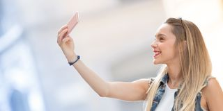 Pretty blonde teenager taking a selfie with her mobile phone. Ho. Rizontal size with copy space on the leftas Royalty Free Stock Image