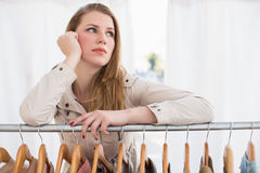 Pretty blonde thinking through clothes rail Royalty Free Stock Photography