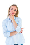 Pretty blonde thinking with hand on chin Royalty Free Stock Photography