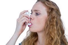 Pretty blonde using an asthma inhaler Royalty Free Stock Photos