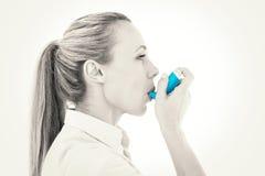 Pretty blonde using an asthma inhaler stock photo