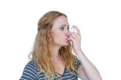 Pretty blonde using an asthma inhaler Stock Images
