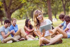 Pretty blonde using tablet in the park Stock Image