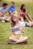 Pretty blonde using tablet in the park Stock Photography