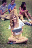 Pretty blonde using tablet in the park Stock Photo