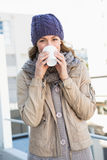 Pretty blonde in warm clothes drinking hot beverage Stock Images