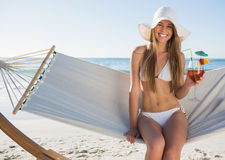 Pretty blonde wearing bikini and sunhat sitting on hammock with Stock Image